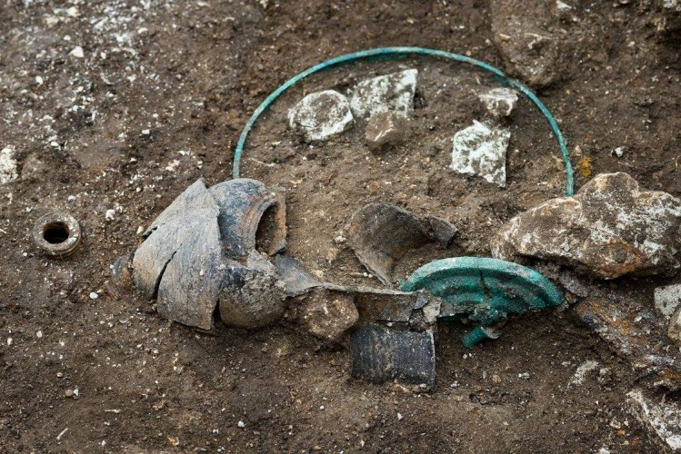 Détail du dépôt funéraire: ici, une bouteille en céramique, un bassin en bronze et un couvercle. Fouille de Lavau (Aube), 2015. © Denis Gliksman, Inrap