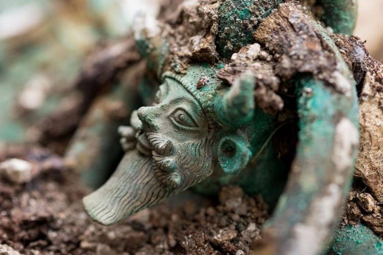 Au fond de la tombe, découverte d'un chaudron en bronze, aux anses décorées du dieu Acheloos. Fouille de Lavau (Aube), 2015. © Denis Gliksman, Inrap