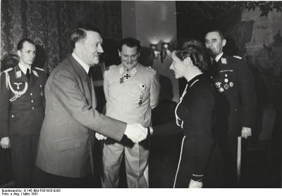 März 1941: Adolf Hitler verleiht Flugkapitän Hanna Reitsch das Eiserne Kreuz [2. Klasse] Mitte: Hermann Göring