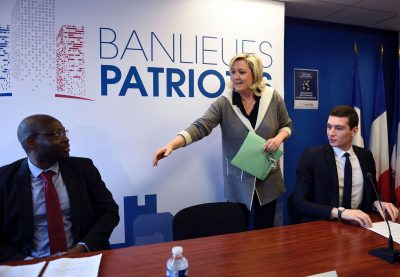 "French far-right Front National (FN) party president Marine Le Pen (C) arrives to delivers a press conference with FN members Guy Deballe (L) and Jordan Bardella (R) during the launch of the new FN collective ""Banlieues patriotes"" (Patriotic Suburbs) at the FN headquarter on January 26, 2015 in Nanterre, west of Paris. Le Pen advocated a global ""national policy"" rather than a specific ""city"" policy regarding suburbs during the launch of the Patriotic Suburbs collective on January 26, of which 20-year-old Ile de France regional council member, elected in Seine-Saint-Denis, Jordan Bardella which be the president. / AFP / ERIC FEFERBERG"