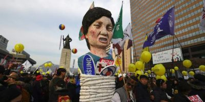 Protesters carry an effigy of South Korea's President Park Geun-Hye during a rally against Park in central Seoul on December 3, 2016. Hundreds of thousands of protestors marched in Seoul for the sixth-straight week on December 3, to demand the ouster and arrest of scandal-hit President Park Geun-Hye ahead of an impeachment vote in parliament. / AFP PHOTO / JUNG Yeon-Je